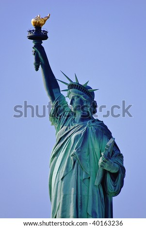 Statue of Liberty standing tall in New York's harbor (designed by French sculptor Frederic-Auguste Bartholdi). One of America's most famous landmarks and known the world over. New York, New York. - stock photo