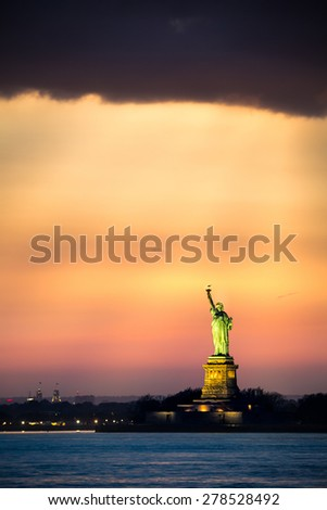 Statue of Liberty under a dramatic sunset light, as viewed from Brooklyn, New York - stock photo