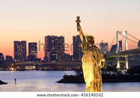 Statue of Liberty with Rainbow Bridge, Tokyo Tower and Tokyo City in Background at Night - stock photo