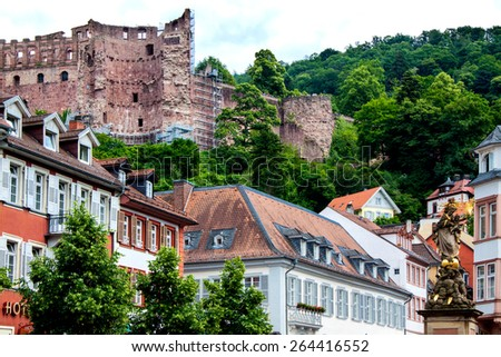 Statue of Madonna Mary and Jesus in town square of old town city of Heidelberg Germany with castle walls background  - stock photo