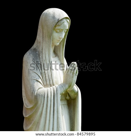 Statue of Mary praying in profile with isolation path and isolated against black - stock photo