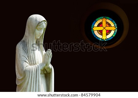 Statue of Mary praying in profile with isolation path and out of focus cross shaped window on the right - stock photo