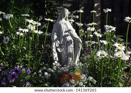 Statue Of The Blessed Virgin Mother Mary In Beautiful Backyard Flower Garden.  Daisies, Petunias
