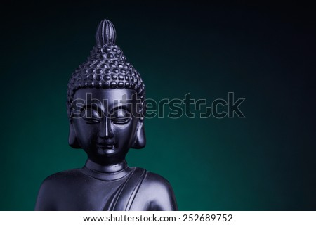 Statue of the Buddah with green back light - stock photo