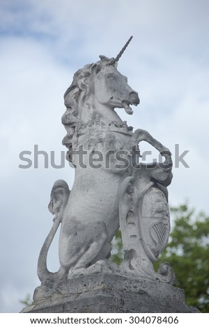 Statue of the mythical creature the Scottish Unicorn with shield and Scottish coat of arms sitting on gatepost outside Buckingham Palace London UK symbolising the free union of Scotland and England.  - stock photo