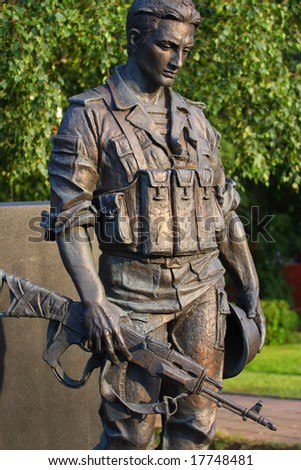 Statue of the soldier. Green background - trees. - stock photo