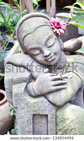Statue of Traditional Thai girl with red flower in the garden - stock photo