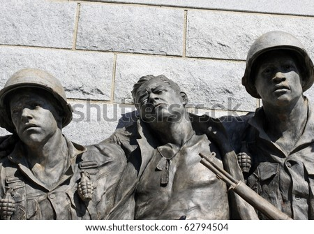 Statue of two soldiers helping an injured soldier emphasis on faces. - stock photo