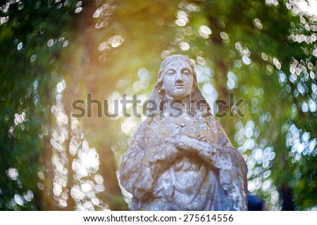 Statue of Virgin Mary at Rasu cemetery in Vilnius, Lithuania. Shot taken with a soft focus lens, shallow depth of field and lens flare - stock photo