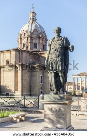 Statue Roman Emperor in with church in Rome, Italy - stock photo