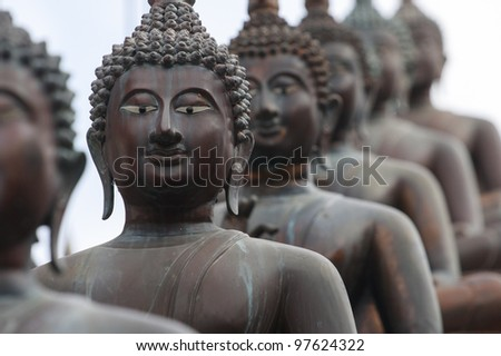 Statues of Buddha in a row - stock photo