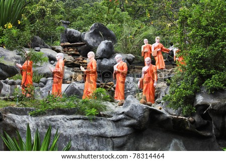 Statues of Buddhist Monks, queuing to take lotus flower offerings to Buddha, at the Rock Temple of Dambulla, Sri Lanka - stock photo