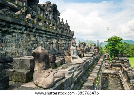 Statues on one of the intermediate levels of the buddhist temple Borobudur, a UNESCO World Heritage site, in Central Java, Indonesia. - stock photo