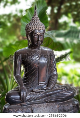 statuette of Buddha in a background of green foliage - stock photo