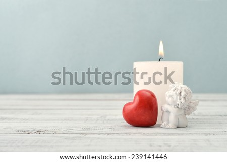Statuette of small  angel with stone heart and candle over light background - stock photo