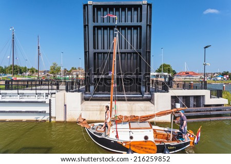 STAVOREN, THE NETHERLANDS - SEPTEMBER 4, 2014: Classic wooden sailing boat passing the Stavoren sluice with open bridge in the province of Friesland, The Netherlands - stock photo