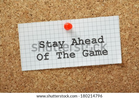 Stay Ahead of the Game typed on a piece of graph paper and pinned to a cork notice board. In business this means staying ahead of your competitors and working to anticipate market forces. - stock photo