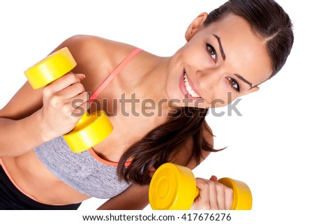 Stay focused on your training. Portrait of a healthy young woman working out with dumbbells and smiling at you. - stock photo