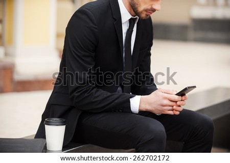 Staying connected anytime and anywhere. Cropped picture of young man in formalwear holding mobile phone while sitting outdoors  - stock photo