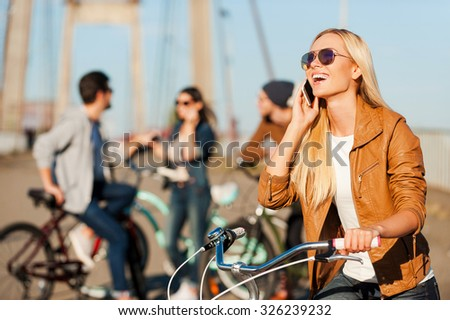 Staying connected. Beautiful young smiling woman leaning at her bicycle and talking on the mobile phone while her friends standing in the background  - stock photo