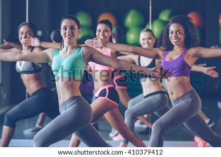 Staying fit and cheerful. Side view of beautiful young women with perfect bodies in sportswear exercising and looking at camera with smile at gym  - stock photo