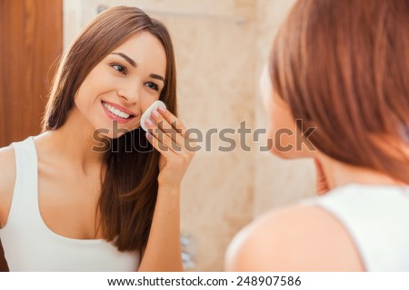 Staying fresh and clean. Beautiful young woman touching her face with sponge and smiling while standing in front of the mirror - stock photo