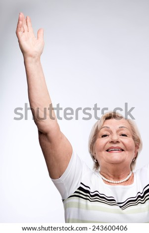 Staying healthy and fit. Closeup portrait of smiling elderly woman raising her hands high above head while standing against white background - stock photo