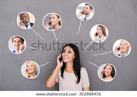 Staying in touch. Beautiful young woman talking on the mobile phone and smiling with portraits of diverse people upon her head - stock photo
