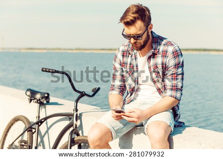 Staying in touch while being on vacation. Thoughtful young man holding mobile phone while sitting on parapet near his bicycle  - stock photo