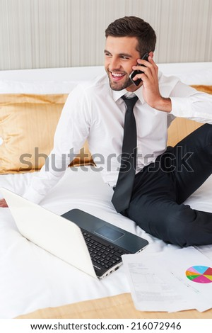 Staying in touch with colleagues. Cheerful young man in shirt and tie working on laptop and talking on the mobile phone while sitting in bed at the hotel room  - stock photo