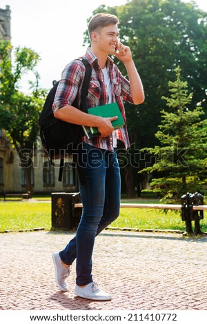 Staying in touch with friends. Full length of handsome male student talking on the mobile phone and smiling while walking outdoors - stock photo
