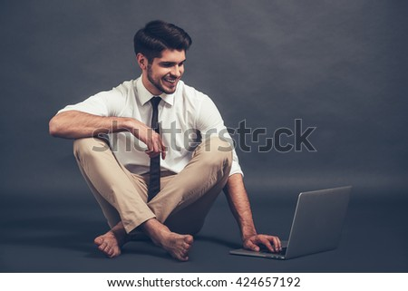 Staying online. Full length of confident young handsome man using laptop with smile while sitting on the floor against grey background - stock photo