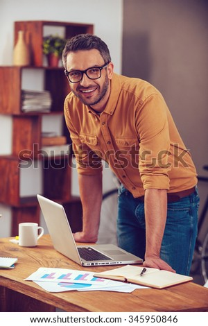 Staying positive in any situation. Handsome young man looking at camera and smiling while standing near his working place in office  - stock photo
