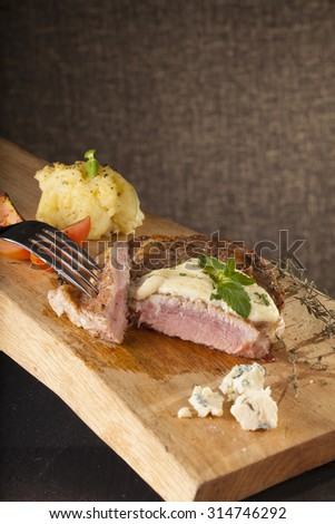 steak, a prepared piece of steak cut with blue cheese sauce on dining table decorated