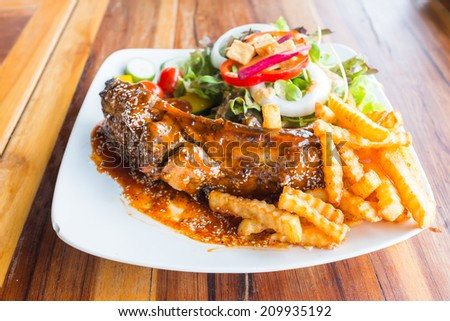 steak barbecue pork  spareribs with sauce sesame on topping vegetable and french fries on white dish on wood table in restaurant - stock photo