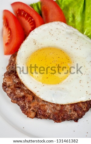 steak beef meat with fried egg, tomato, cucumbers and salad - stock photo