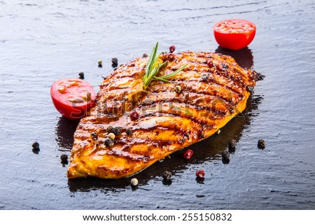 Steak chicken breast olive oil cherry tomatoes pepper and rosemary herbs. - stock photo
