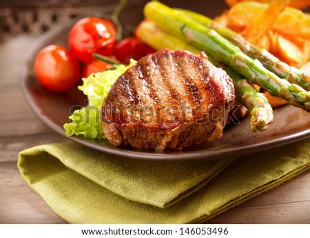 Steak Dinner. Grilled Beef Steak Meat with Fried Potato, Asparagus and Cherry Tomato. Food