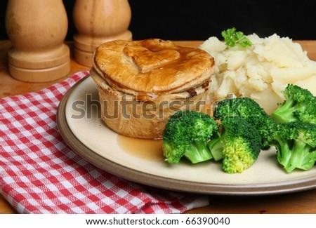 Steak & kidney pie with mashed potato, broccoli and gravy. - stock photo