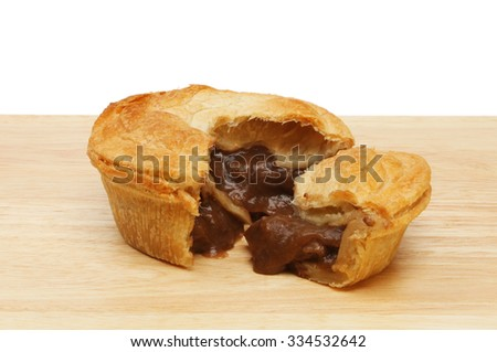 Steak pie with a slice cut out on a wooden board