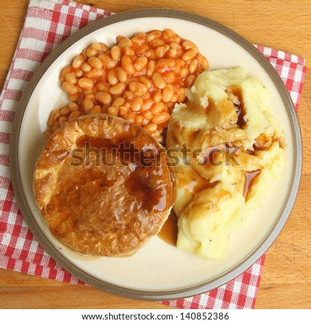 Steak pie with baked beans, mashed potato and gravy. - stock photo