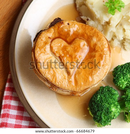 Steak pie with mashed potato, broccoli and gravy. - stock photo