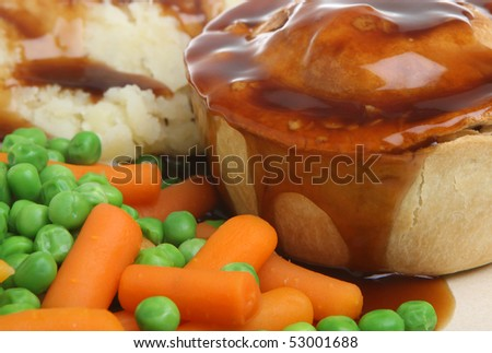 Steak pie with mashed potato, peas, carrots and gravy. - stock photo