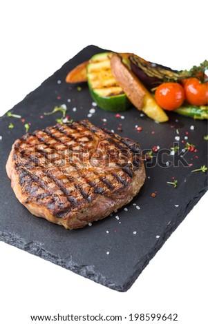 Steak rib-eye garnished with grilled vegetables isolated on white background - stock photo