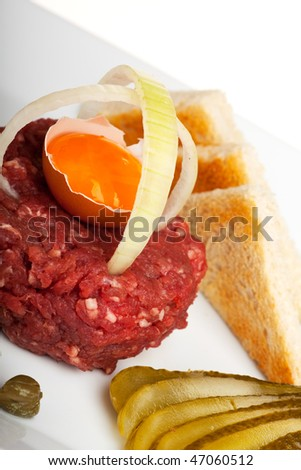 steak tartar with an onion ring and an open egg