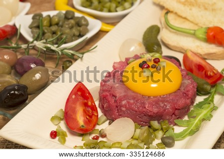 Steak Tartare with garnishes on on a plate - stock photo