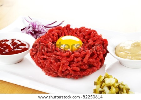 Steak tartare with yolk on white plate with onions, pickles, mustard and ketchup. Toast in background. - stock photo