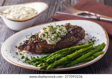 Steak with blue cheese sauce served with asparagus on dark background.