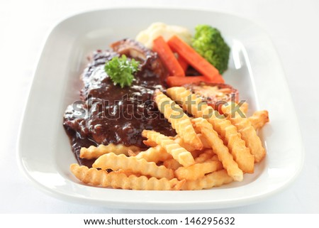 Steak with gravy served with fries and vegetable sides
