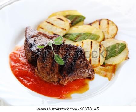 Steak with tomato sauce, potatoes and sage - stock photo